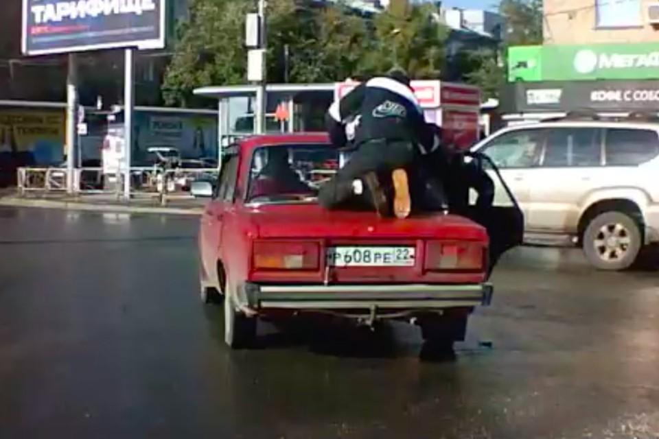 Более минуты мужчина находился на крыше автомобиля. Фото: стоп-кадр с видео